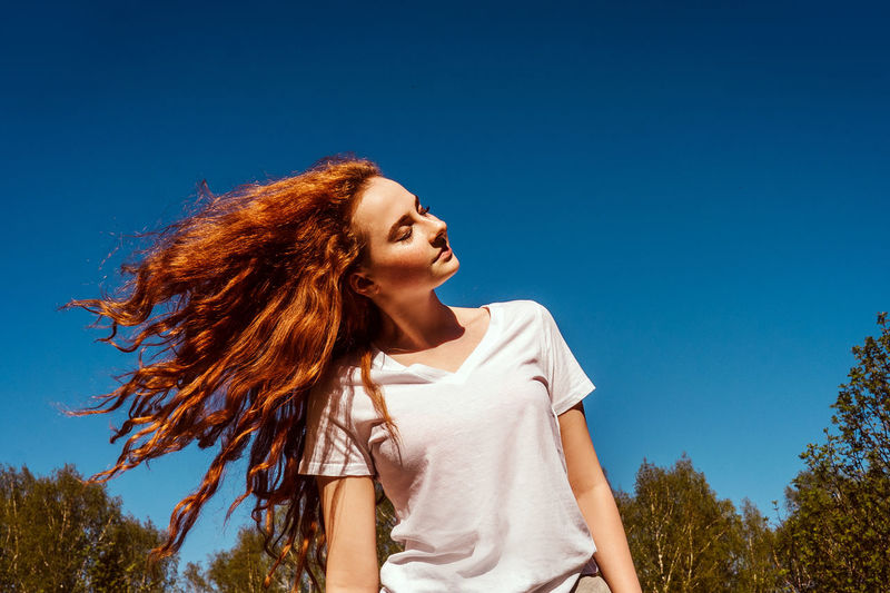 Low angle view of girl tossing hair against sky