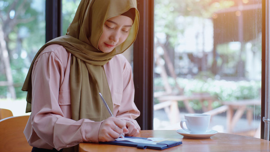 Young woman in hijab writing on paper while sitting at cafe
