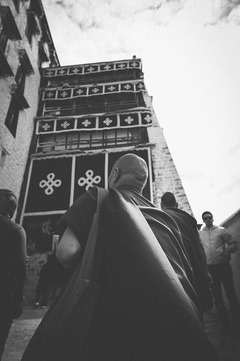 Monk at Lhasa Monk  Tibetan  Outdoors City Lifestyles Rear View Place Of Worship Men Day Low Angle View Building Sky People Women Built Structure Building Exterior Belief Real People Group Of People Spirituality Religion Architecture EyeEm Selects