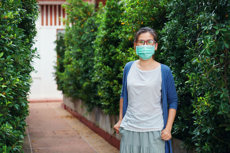 A woman wears a mask in a public park when going outdoor during covid-19 pandemic