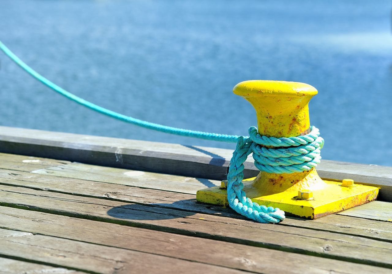 Close-Up Of Yellow Rope Tied To Wooden Jetty