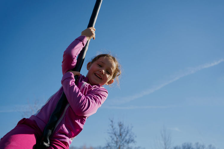 Low angle view of girl playing against sky