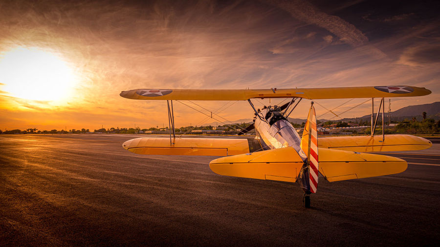 Airplane at runway against sky during sunset