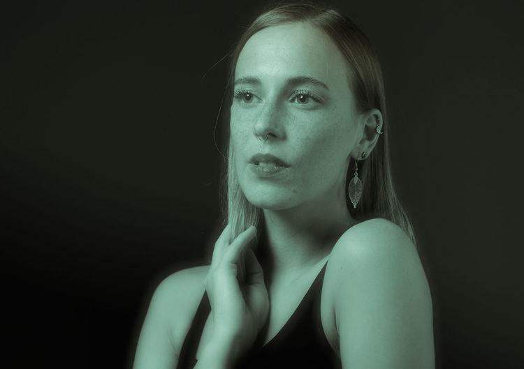 Beautiful woman looking away against black background