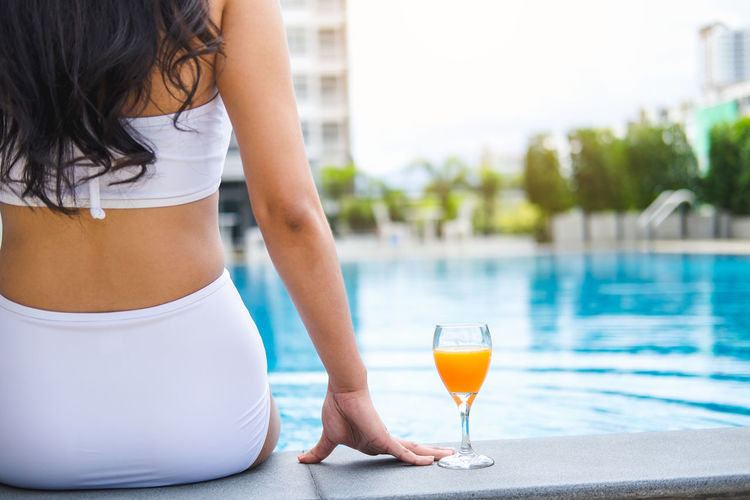Midsection of woman with orange juice sitting at poolside