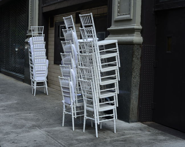 Stacked Chairs On Footpath Against Building