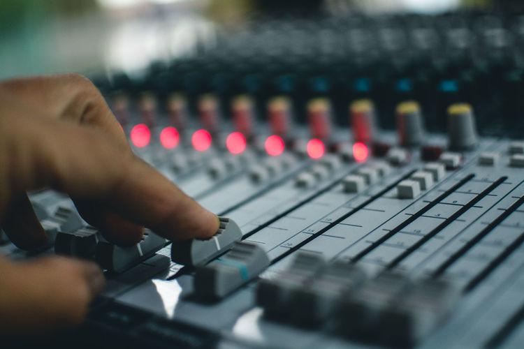 Close-up of human hand adjusting sound mixer in nightclub