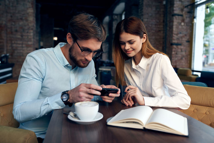 Young man and woman using phone in cafe