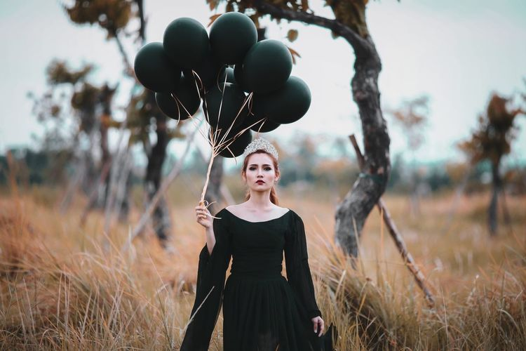 Portrait of woman with balloons standing on field