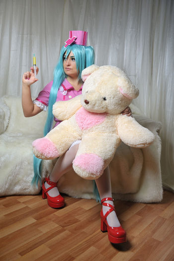 Young Nurses With Long Blue Hair Injecting Syringe To Teddy Bear At Home