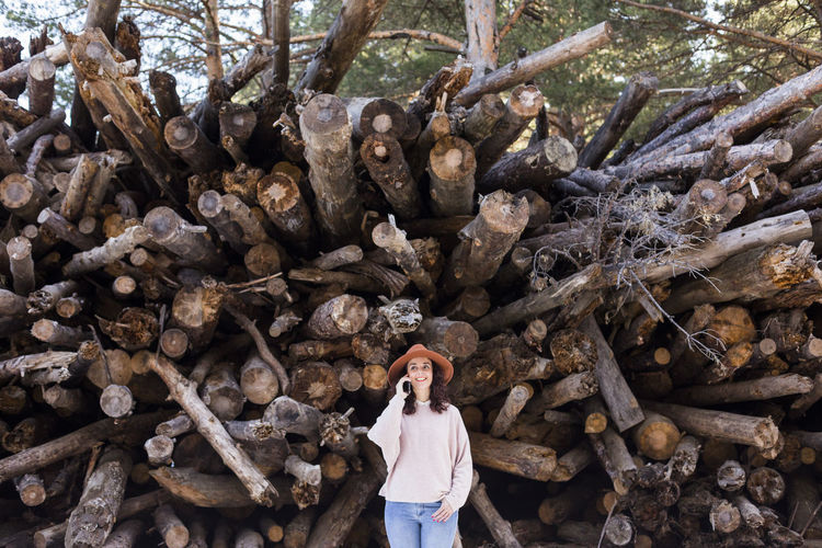 Smiling woman using smart phone while standing against woodpile in forest
