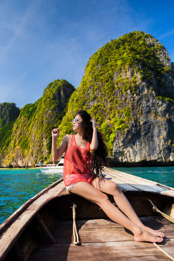 Beauty In Nature Day Full Length Hair Hairstyle Leisure Activity Lifestyles Mountain Nature Nautical Vessel One Person Outdoors Real People Scenics - Nature Sea Sitting Sky Water Women Young Adult Young Women