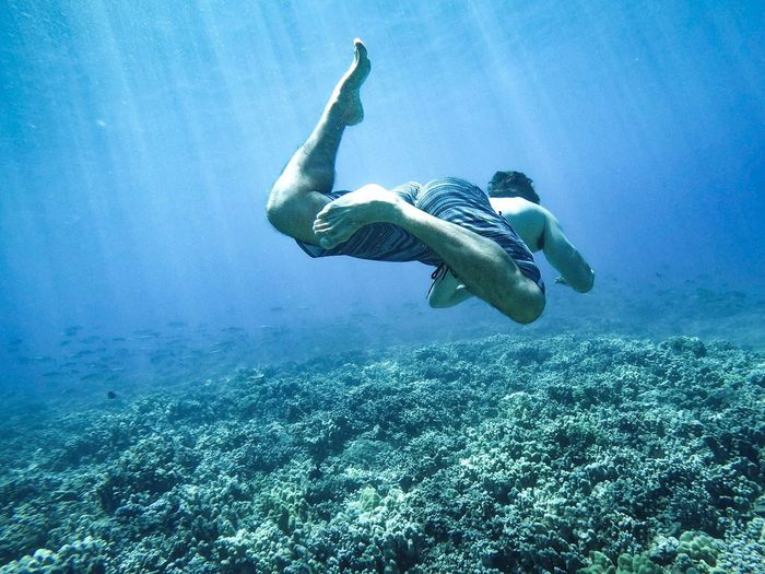 Man swimming underwater in sea
