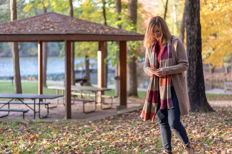 Full length of woman standing in park during autumn