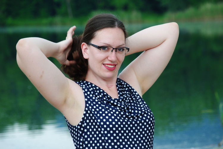 Portrait Of Smiling Woman Tying Hair Against Lake