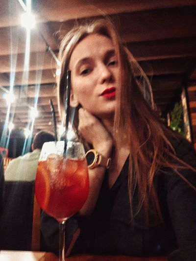 Portrait of woman drinking glass in restaurant