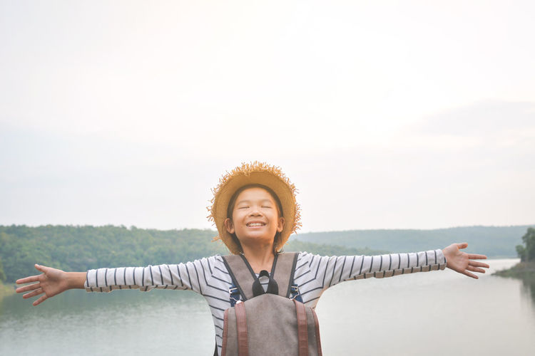 Smiling Boy Standing Against Sky