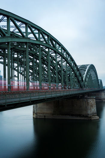 View of the Hohenzollern Bridge and a passing Train. Train Bridge Transportation Connection Architecture Germany Hohenzollernbridge Hohenzollernbrücke Köln Rhine River Water Cloudy Cold Temperature Long Exposure No People Outdoors Railway Bridge City Girder Bridge - Man Made Structure Built Structure Europe Reflection Cloud - Sky Nature Waterfront Day Sky