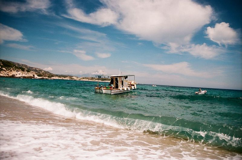 Fisherman's boat on the shore in Chalkidiki peninsula Analogue Photography Holidays Beauty In Nature Boat Chalkidiki Cloud - Sky Clouds Day Fisherman Fisherman Boat Greece Horizon Over Water Mountain Nature Nautical Vessel Outdoors Sea Sky Space Tranquility Village Water Waterfront Wave Waves