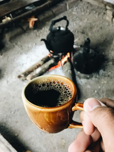 High angle view of hand holding coffee cup