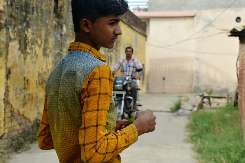 Close-up of boy standing on road in village