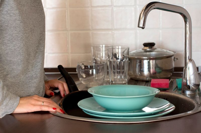 Midsection of woman cleaning plates in kitchen at home