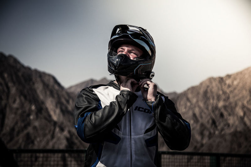 Man putting on motorbike helmet Adults Only Bike Day Gear Gear Up Helmet Icon Jacket Men Motorbike Motorsport Mountains One Man Only Only Men Outdoors Protection Race Racer Real People Scenics Sky Speed Sport