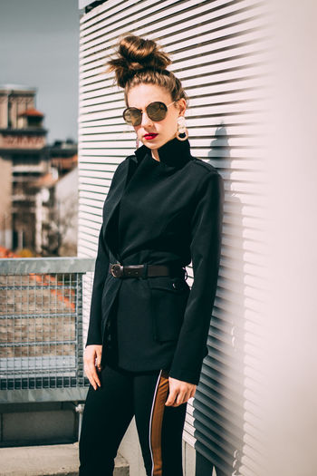 Portrait of fashionable woman wearing sunglasses while standing in city