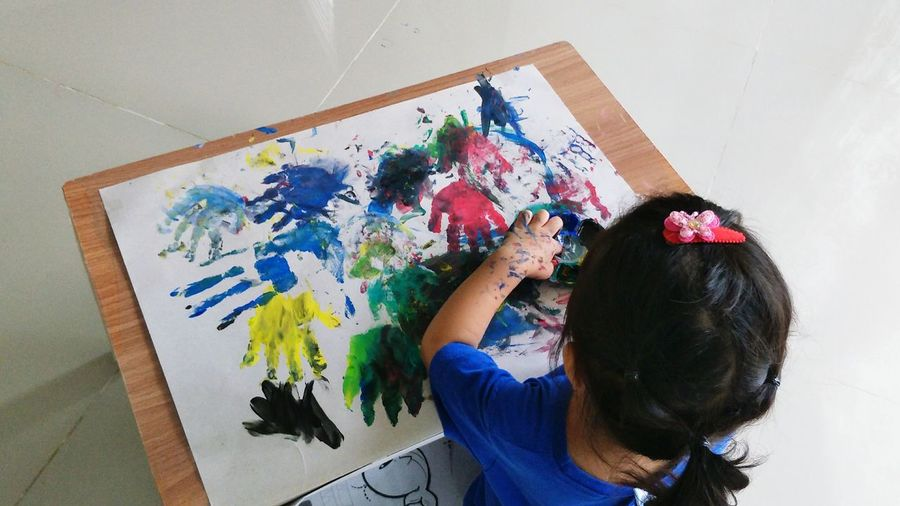 High angle view of girl painting on paper at home