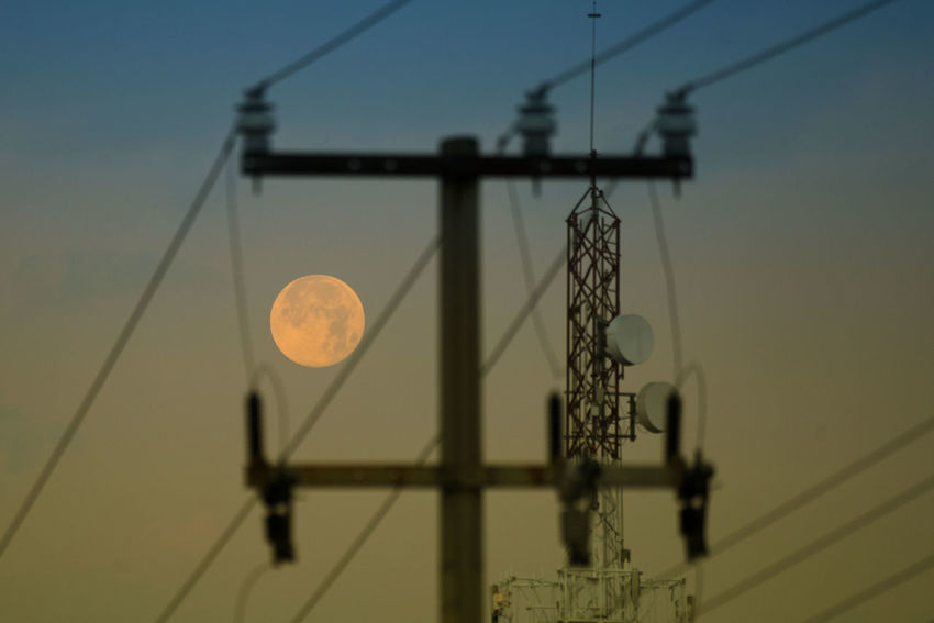 View of the full moon at dawn. Astronomy Cable Clear Sky Communication Connection Day Electricity  Electricity Pylon Low Angle View Moon Nature No People Outdoors Sky Sunset Technology