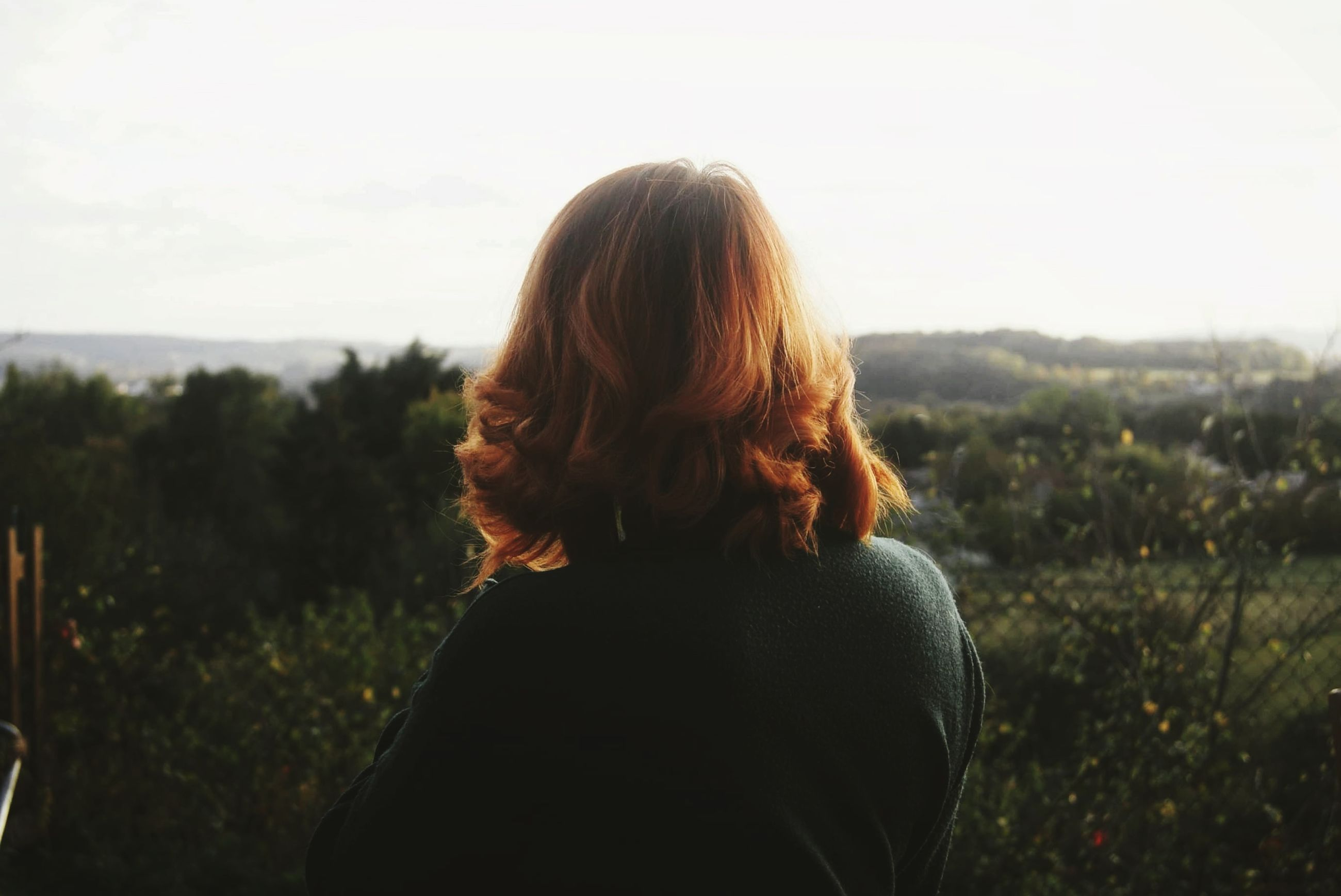 one person, rear view, hair, real people, hairstyle, sky, leisure activity, lifestyles, women, adult, standing, nature, long hair, blond hair, focus on foreground, young adult, beauty in nature, plant, waist up, looking at view, outdoors