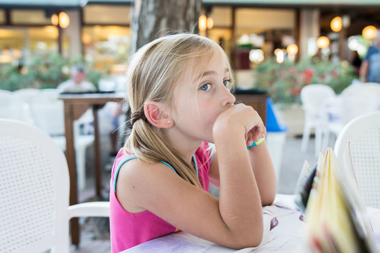 waiting in the restaurant Sitting Waiting Blond Hair Casual Clothing Chairs Child Girl Outside Portrait Real People Restaurant Summer Tables Cute Lovely Family Children Only