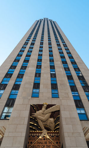 Low angle view of Rockefeller Center in NYC Business Financial District  Manhattan NYC New York New York City Rockefeller Center Rockefeller Plaza Architectural Column Architecture Art And Craft Blue Building Building Exterior Built Structure City Clear Sky Day Human Representation Low Angle View Nature No People Office Building Exterior Representation Sculpture Sky Statue Tall - High Travel Destinations
