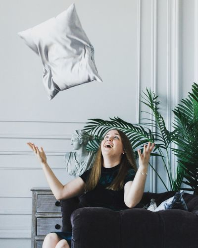 Young woman throwing pillow in air at home