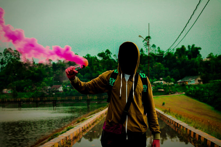 Man wearing hooded shirt while holding pink distress flare