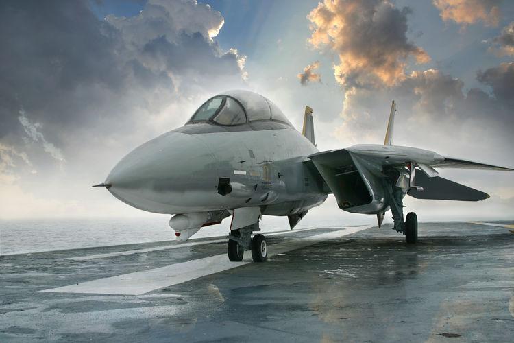 Grumman F-14 Tomcat Airplane On Runway Over Sea Against Cloudy Sky