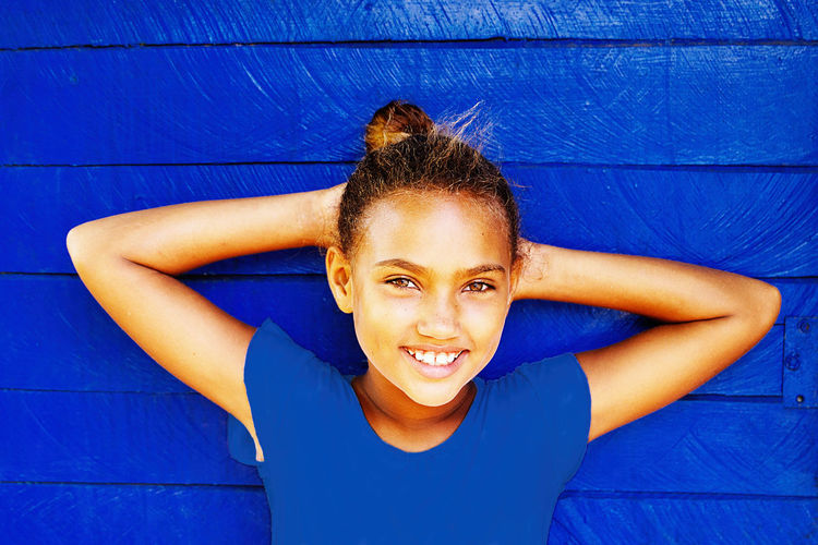 Portrait of a smiling girl against blue wall