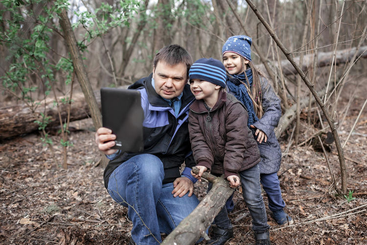 Smiling kids with father talking on video call in forest