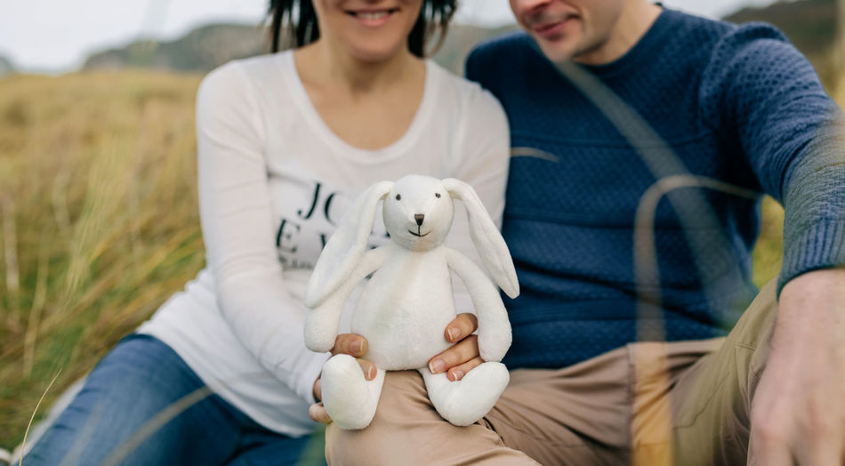 Midsection Of Woman With Man Holding Stuffed Toy On Field