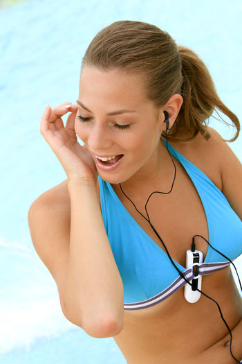 young blond woman listening to music with MP3 players at the pool Beautiful Happy Holiday Listening Music Music Summer Holidays Woman Beautiful Woman Bikini Blond Girl Happyness Leisure Leisure Activity Lifestyles Mp3 Player One Person Pretty Relaxation Swimming Pool Vacation Water Wellbeing Young Adult Young Women