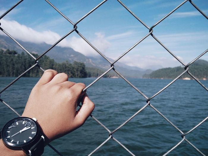 Cropped hand holding chainlink fence against river