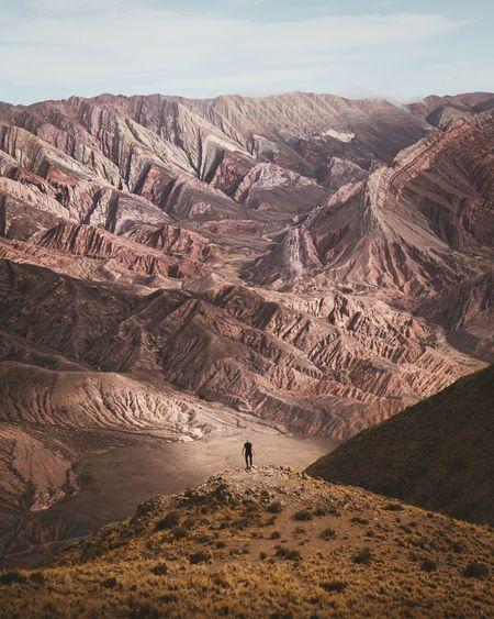 Man on cliff against mountain range
