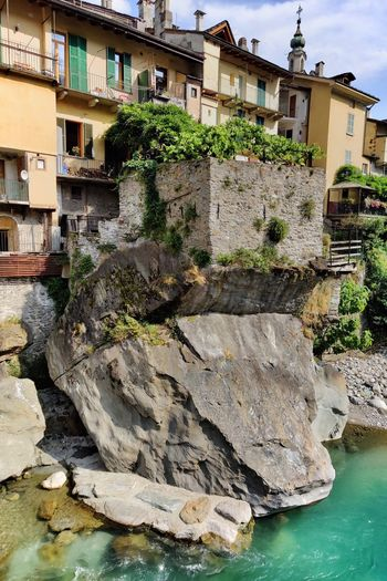 Rocks by river against buildings