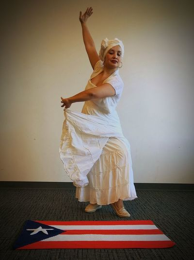 Full length of female dancer by puerto rican flag against wall