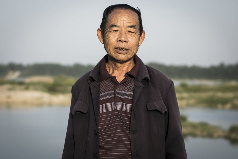 Portrait of man standing by lake against sky