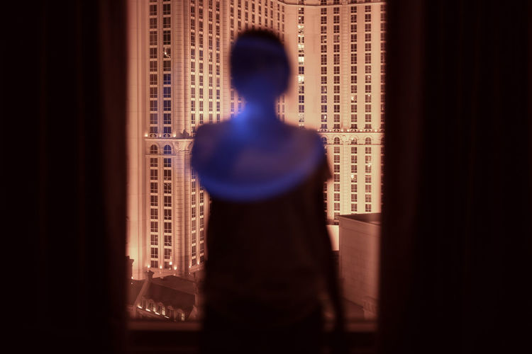Rear view of silhouette man standing by window at home