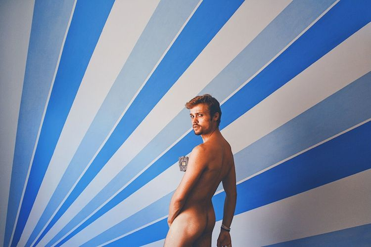 Portrait of naked young man standing against wall