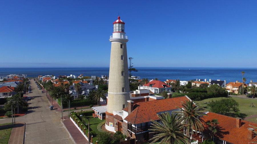 Lighthouse amidst buildings and sea against clear blue sky