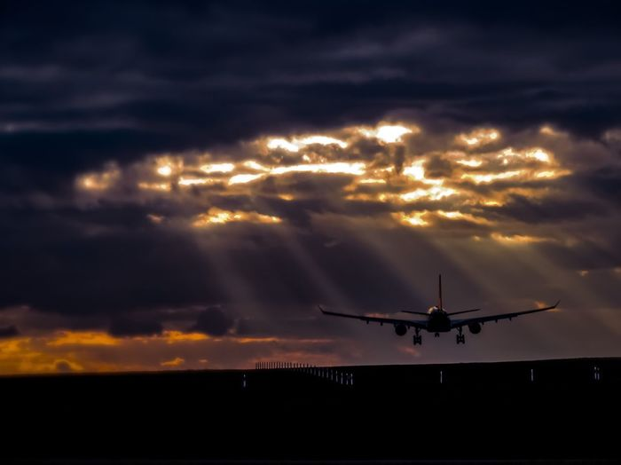Silhouette airplane flying in sky during sunset