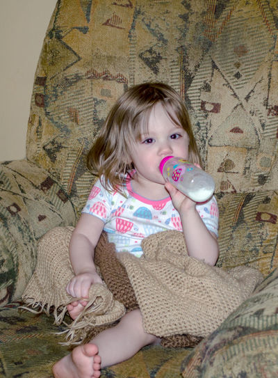 Full Length Of Cute Girl Drinking Milk On Chair At Home